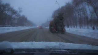 car goes down the road in winter snow.