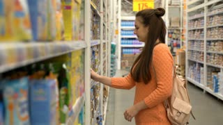 Footage Young mom buys baby food in supermarket.