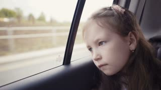 Little girl looking out from car window at sunny day.