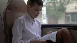 shot of a young schoolboy traveling by bus through city and reads a book.