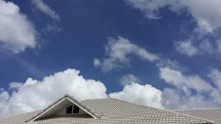 time lapse beautiful clouds move fast over roof of the house