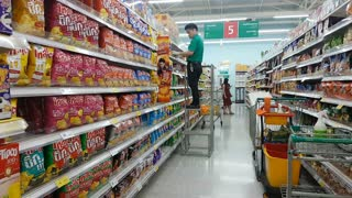 CHIANG RAI, THAILAND SEPTEMBER 26: unidentified asian male worker arranging goods on the shelf at superstore on September 26, 2018 in Chiang rai, Thailand.
