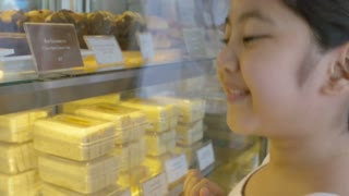 4K : Asian girl looking at display window with different cakes