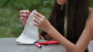 4K : Asian girl practices to sewing a dress for her doll with needles and thread