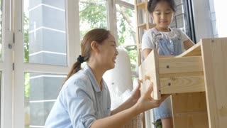 4K : Asian lovely girl helping her mother assembling new DIY furniture at home together