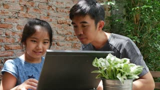 4k : Asian man teaching his daughter for using computer laptop