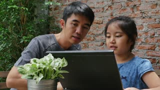 4k : Asian man teaching his daughter for using computer laptop