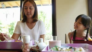 4K : Asian mother feeding sushi for her daughter in a restaurant with smile face, Happy asian family concept.