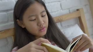 4K : Asian preteen girl reading story book on the bed