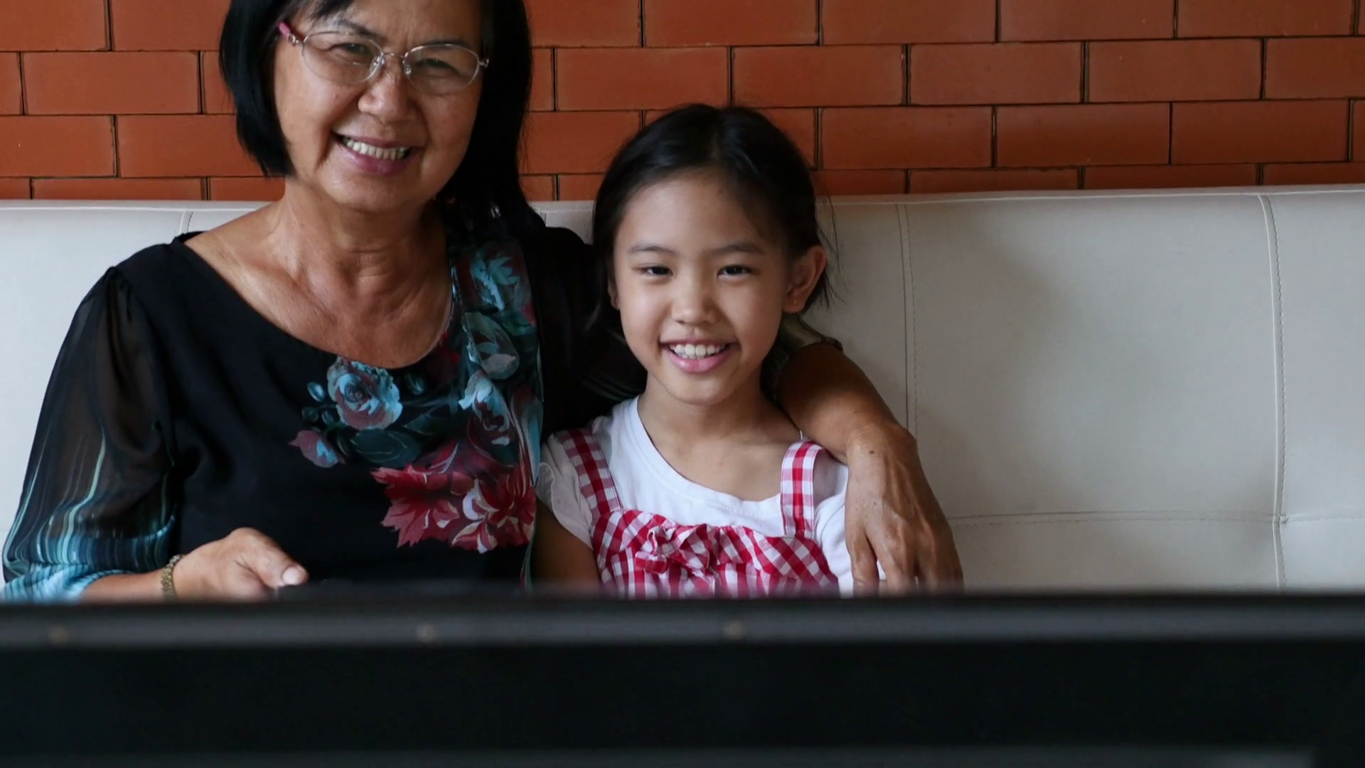 4K : Asian senior woman with little girl watching TV on sofa together, Tilt up shot Stock Video Footage - Storyblocks