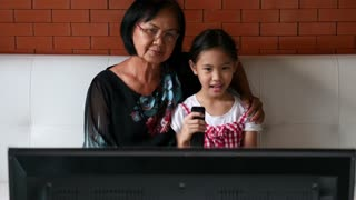 4K : Asian senior woman with little girl watching TV on sofa together, Tilt up shot