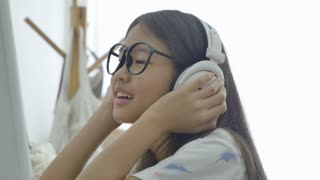 4K : Attractive Asian girl listening music on computer with headphone in the room, Pan shot