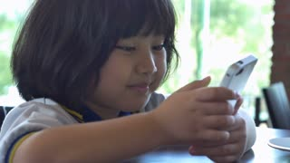 4K : Close up of Asian child playing game on smart phone together