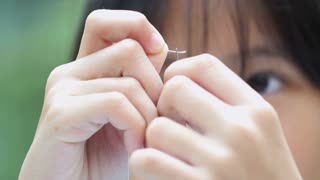 4K : Close up of Asian girl practices to sewing a dress for her doll with needles and thread