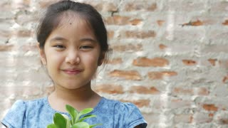 4K : Close up of Happy Asian child showing a little green plant, Green environment concept