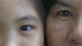 4K : Close up on eyes of Asian girl and senior woman faces