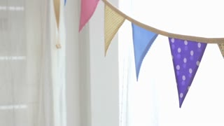 4K : Dolly shot of colorful party flags bunting hanging on white wall for holiday decoration