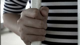 4K : Hands of the Asian prisoner behind the jail