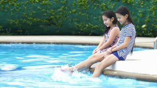 4K : Happy Asian girl  splashing water with their feet in summer