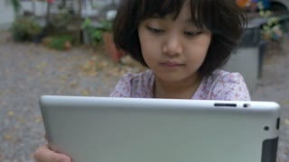 4K : Happy Asian girl watching cartoon on digital tablet