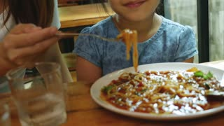 4K : Happy Asian mother feeding delicious spaghetti for her daughter