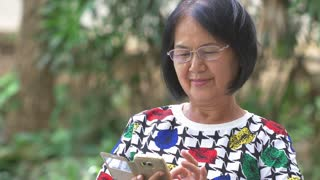 4K : Happy Asian senior woman touching the smart phone