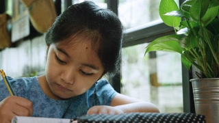 4K : Little Asian child doing her exercise workbook, Education concept