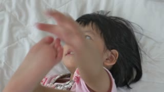 4K : Little Asian child laying and playing on the bed