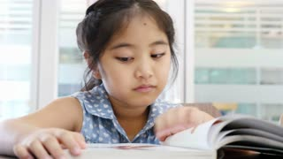 4K : Little Asian girl reading a book in library