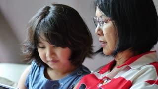 4K : Little Asian girl using digital tablet with her grandmother together