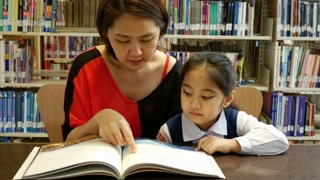 4K : Little Asian students and teacher reading book in library together