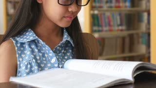 4K : Little Asian students reading a book in library, Tilt up shot