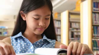 4K : Little Asian students reading a book in library, Zoom out shot