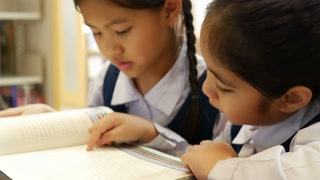 4K : Little Asian students with uniform reading book in library together, tilt up camera