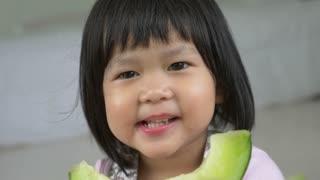 4K : Lovely Asian child girl eating delicious green melon