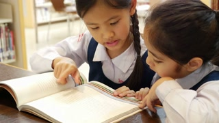 4K UHD : Little Asian students with uniform reading book in library together, tilt up camera