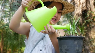 4K video of a happy Asian girl watering her plant in the garden