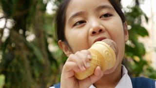 4K Video of little Asian girl enjoying her ice cream