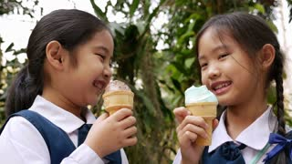4K Video of little Asian girls enjoying ice cream together