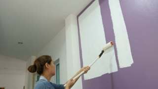 4K : Young Asian woman painting the wall in her apartment