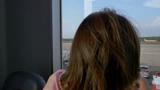 Asian child and her mother looking at airplanes in the airport