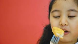 Asian child enjoying chicken nugget