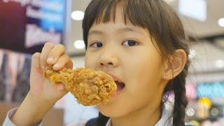 Asian child enjoys eating fried chicken