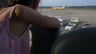Asian child looking at airplanes in the airport.