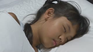 Asian child sick and sleeping on the bed with her mother by her side.