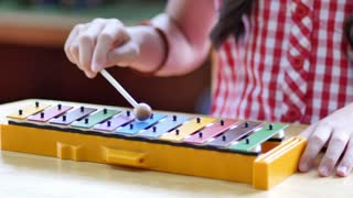 Asian Children playing on colorful xylophone