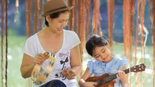Asian daughter playing ukulele with her mother in park