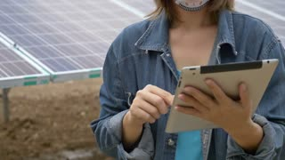 Asian engineer checking solar panel setup with tablet, Tilt up shot