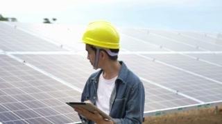 Asian engineer walking to check solar panel setup