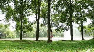 Asian family behide the tree and running together in the park, Slow motion